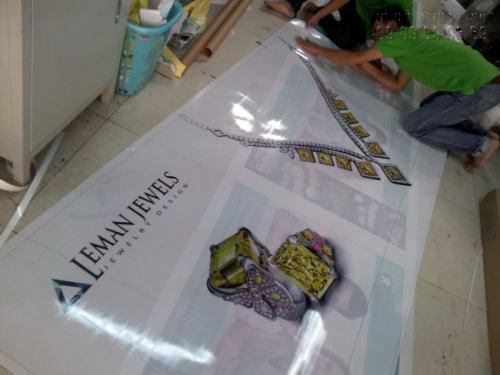 Nhân viên In Kỹ thuật số đang gia công thành phẩm in backlit film cho nhãn hàng thời trang cao cấp Leman Jewels