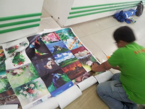 Nhân viên In Kỹ Thuật Số đang gia công thành phẩm in tranh sơn dầu trên nền vải canvas cho khách hàng