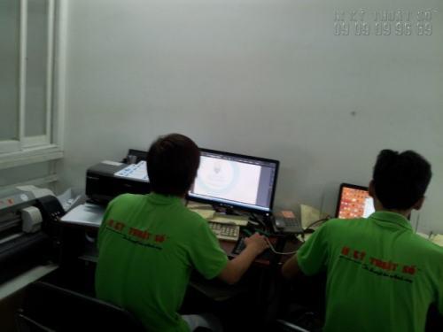 Nhân viên thiết kế hỗ trợ khách hàng kiểm tra file thiết kế trước khi chạy đơn hàng in