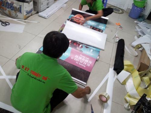 Lắp poster quảng cáo vào banner cuốn cho khách hàng