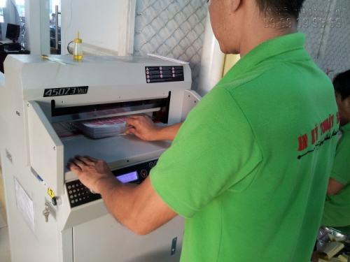 Nhân viên InKyThuatSo đang gia công cắt tem decal trong bằng máy cắt lazer