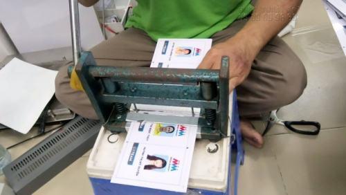 Nhân viên InKyThuatSo đang tiến hành gia công đục lỗ 4 góc cho thẻ nhân viên đặt in từ khách hàng