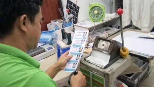 Nhân viên in ấn của InKyThuatSo đang gia công thẻ nhựa cho khách hàng sau khi in xong thẻ nhựa