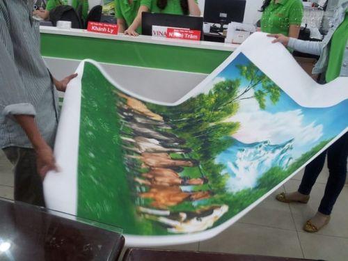 In tranh canvas tại In Kỹ Thuật Số - khách hàng kiểm tra thành phẩm in tranh canvas khi nhận hàng