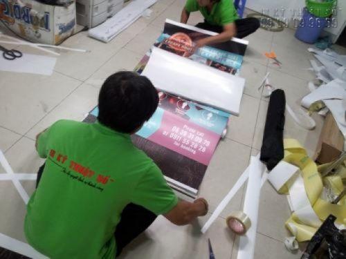 Nhân viên gia công đang lắp poster vào banner cuốn cho khách hàng