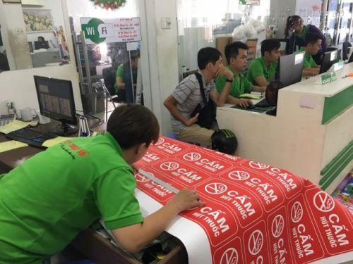 Nhân viên thiết kế in ấn ngồi cùng khách hàng lên mẫu thiết kế in menu quán ăn