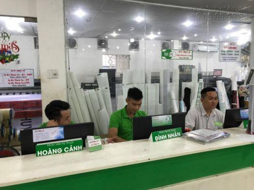Nhân viên thiết kế in ấn ngồi cùng khách hàng lên mẫu thiết kế in menu quán cafe