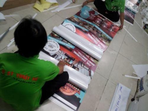 Nhân viên gia công In Kỹ Thuật Số lắp sẵn poster vào banner cuốn - bạn chỉ cần kéo lên và trưng bày