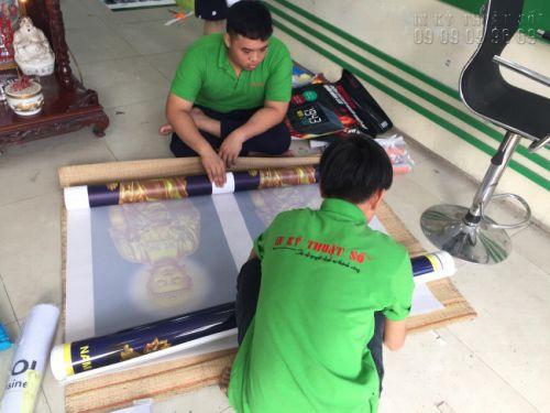 Nhân viên gia công In Kỹ Thuật Số cẩn thận cuộn thành phẩm in backlit film thành cây tròn, trước khi đóng gói vào hộp giấy vận chuyển