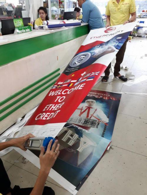 Công đoan thực hiện gia công lắp poster vào banner cuốn bởi nhân viên gia công In Kỹ Thuật Số